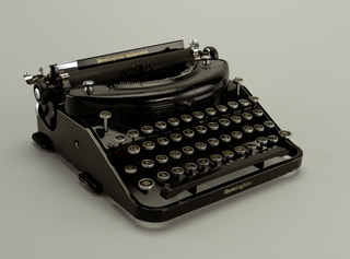 A Remington noiseless portable typewriter in a black metal. This typewriter has rounded corners and round black and white keys.