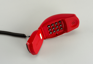 "Red folding ""clamshell"" type telephone opens to reveal black keypad below pierced earpiece in hand set; speaker in base, below hinge; spiral black cord attached to back of base."