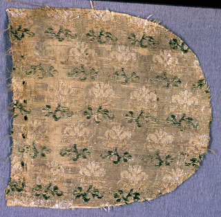 Fragment with one curved edge. pattern of flowers arranged in rows facing in alternate directions.