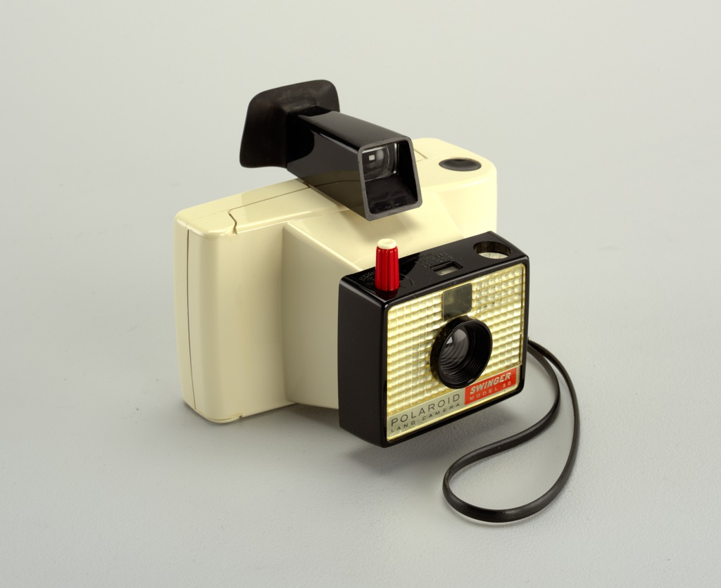 "Rectangular off-white plastic body with black lanyard strap on right, black eyepiece with viewer on top; front with projecting lens within black rectangular frame having red and white shutter button on tope and textured metalic front with text at bottom: ""POLAROID / LAND CAMERA"" and ""SWINGER / Model 20""."