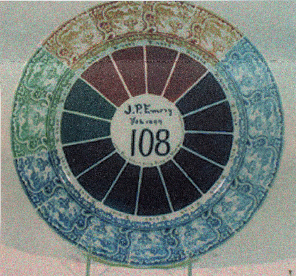 """Circular plate, the shallow well with 15 pie wedge shapes in shades of brown (4), blue (9) and green (2); scalloped rim with repeated, transfer printed decoration of landscape in cartouche and floral border (the hue of each repeat corresponds to wedge of same color); small numbers written in black between transfer decoration and wedges; painted in center of plate: """"J.P.Emery / Feb. 1899 / 108 / From 6145 To 6153 Fired in Slosh [Glosh?] Oven."""""""