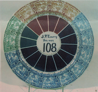 "Circular plate, the shallow well with 15 pie wedge shapes in shades of brown (4), blue (9) and green (2); scalloped rim with repeated, transfer printed decoration of landscape in cartouche and floral border (the hue of each repeat corresponds to wedge of same color); small numbers written in black between transfer decoration and wedges; painted in center of plate: ""J.P.Emery / Feb. 1899 / 108 / From 6145 To 6153 Fired in Slosh [Glosh?] Oven."""