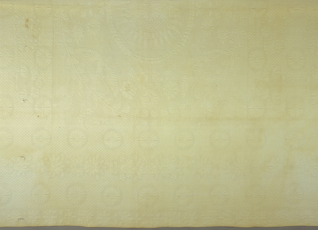 White quilted bedcover in an allover rosette design. In the center, a large circular pattern of a rayed sun. At four points around the circle are four American eagles with shields and arrows.