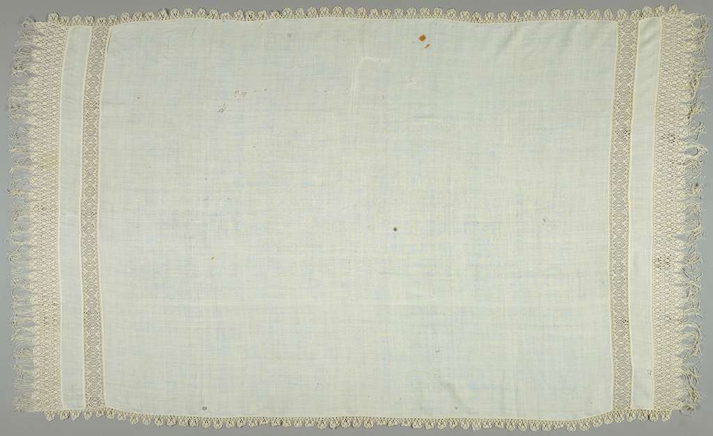 White cover with knotted white linen fringe on all four edges. The fringe was made seperately and applied to the plain weave fabric. At each end there is a an insert of knotted linen, a band of plain weave, and then a wider border of knotted fringe. The edges have been trimmed with scalloped bands of knotted trim.