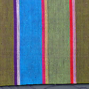 Plain weave in wide vertical stripes of turquoise blue, olive green and yellow-green with pairs of narrow stripes in white and violet, pink and red, and yellow and magenta. The violet threads of the weft give a variegated look to the surface of the textile.
