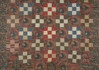 Large-scale pillar pattern in striped effect of reds and blues and reserved white. Design shows an elaborate capital surrounded by fruit and flower clusters. On a strong red ground, festooned baskets containing naturalistic flowers flank pillars. Quilt is lined with a patchwork of the same fabric, other patterned fabrics, and bed ticking.