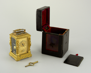 "a)Traveling alarm clock, rectangular in plan, gilded bronze with bevelled glass panels, top and sides, exposing works. Handle on top. Horizontal banding of beading and acanthus leaves, female sheathed figures at four corners. b) Rectangular black leather case lined with red velvet, silk and paper. c) double-ended key for which storage slot is provided in case.  Donor mentions word ""Heberlin"" in connection with this clock."
