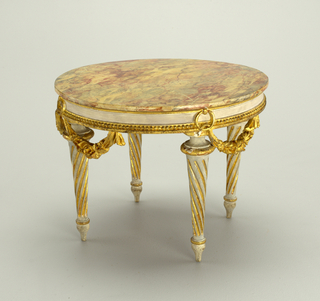 Miniature table made of chestnut with a near circular top marbleized and carved in one piece with frieze rail which has beading on lower edge and free hanging flower garlands suspended by rings.  Four tapering, spirally fluted legs terminating in baluster feet.  Painted grayish white and gilt in parts.