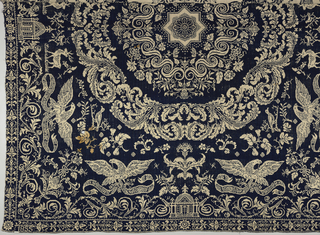 Large complete coverlet in navy blue wool and white cotton with two central wreaths enclosing an eight-pointed star. Surrounding these are an array of floral and bird motifs including eagles with wings spread and clutching banners, scrolling acanthus leaves, a small building with cupola, and pairs of reindeer. Date on coverlet appears to read 1855.