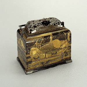 Rectangular black, gold and red lacquered box (a), with hinged, rectangular silver handle; rectangular domed cover (b) of pierced and molded silver, depicting two flying cranes among pine trees, small loop handle in form of branch at top; deep, rectangular brass tray under cover, set into top of box.  Four drawers (d/g) in front of box; one drawer (h) in right side. Continuous lacquer decoration around box showing loaded boat floating on waves, floating dingy, cranes with red crests flying among clouds over water and pine branches.  Drawer pulls in wave motifs, hinged pipe hooks on left and right front, and corner guards at base, all of incised silver.