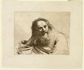 The man, with a large beard, faces frontally. His right elbow is on a table; he rests his head on his right palm.