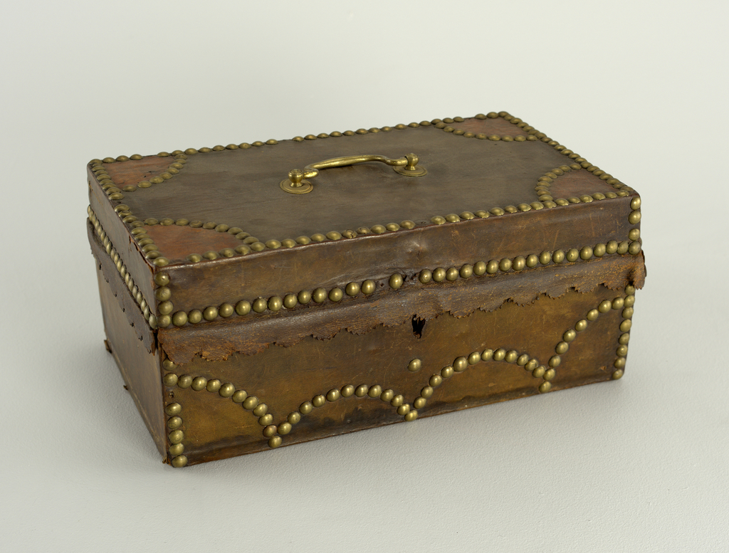 Rectangular box with lock hinged lid: scalloped flap of leather with pinked edge extends from front and sides of lid. Covered with brown leather held down by round-headed brass tacks in edging rows, and scallop patterns. Quarter circles of tan leather, edged with brass tacks, in four corners of top. Bail handle in center of top. Lined with pale blue paper.  American