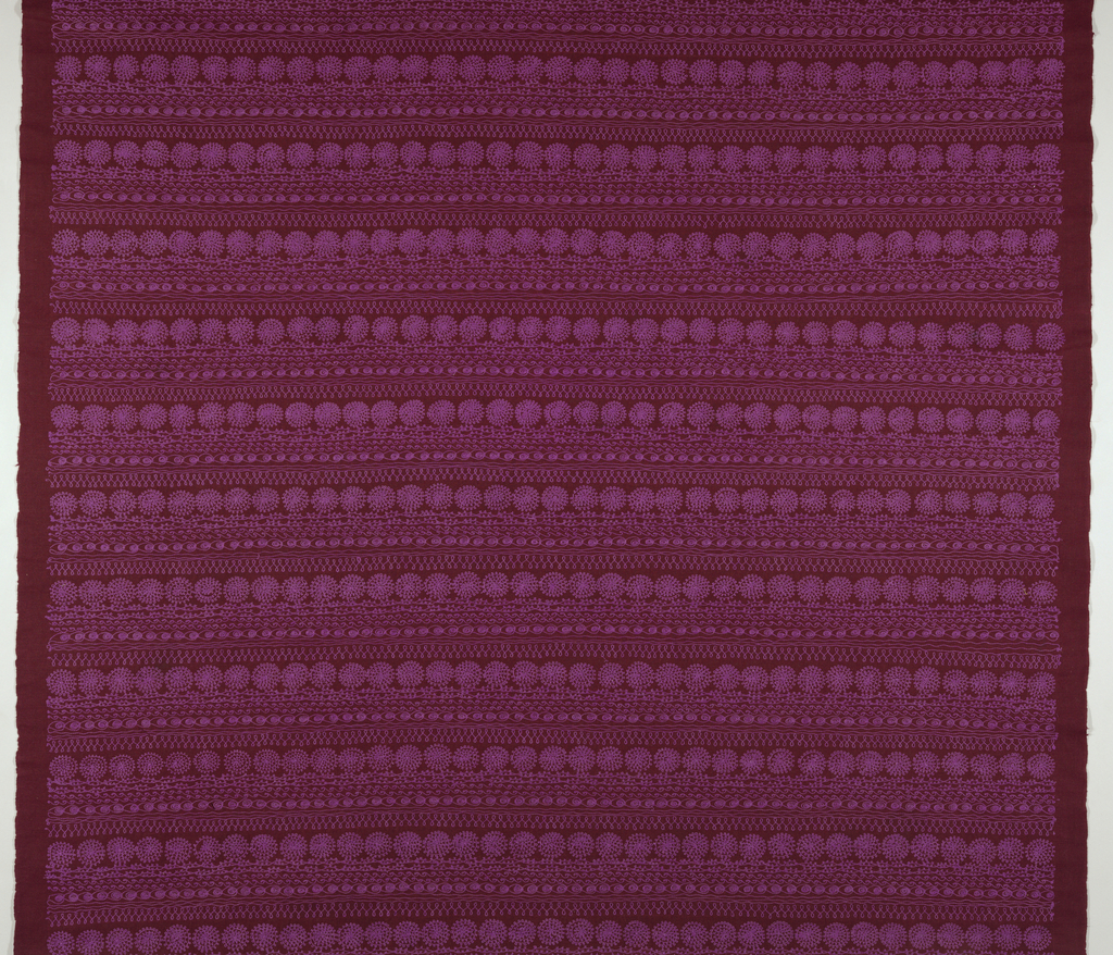 Horizontal bands of embroidery, repeating leaf and wave forms, radiating circles and figure-8 loops in bright fuschia thread on a deep plum ground.