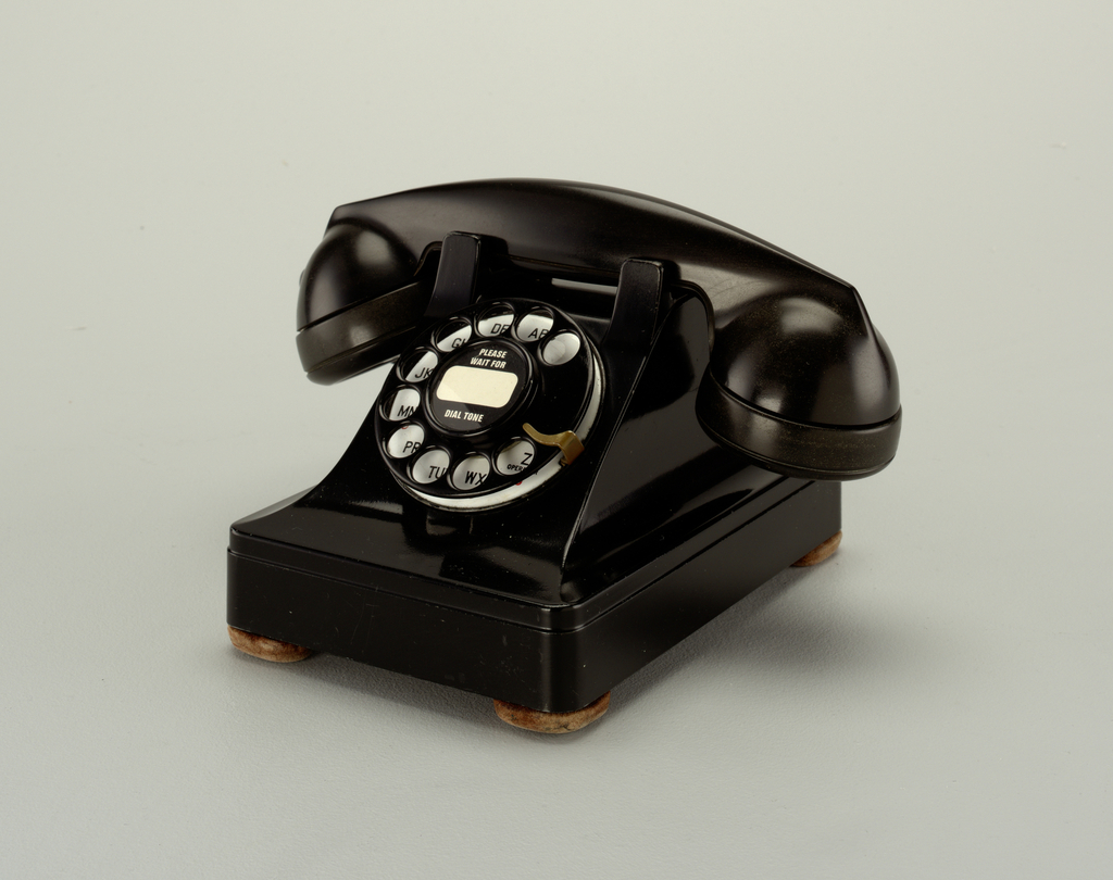 Black rotary telephone; transmitter/receiver handset sitting in cradle on raised body with square base; black metal finger wheel above white dial with black numbers; smooth cord, one end attached to handset transmitter and the other to back of telephone base.