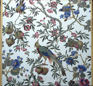 Blossoms and birds on field of pomegranate-bearing branches and flowering vines. In center a pheasant-like bird turns its head upward. Above to the far right and far left are bluebirds. Green leaves, pink and blue blossoms, multicolored pheasant, olive and pink pomegranate; all on white ground.