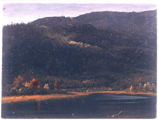 A part of a lake in the forground.  In the background is a hill range and trees with color changing leaves on the lake shore.