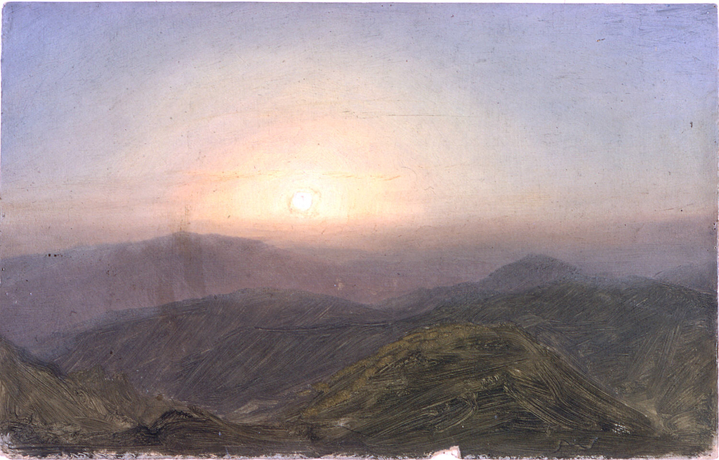 The rising sun in a blue sky is shown over the tops of hills.