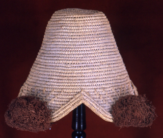 Conical raffia hat with four lobes at the lower edge, each with with a large rust-colored pompom. The hat is formed of simple looping over a foundation element, with longer stitches forming an inverted triangle of twill ornament on each scallop. Three rows of raffia cord are stitched around the bottom using buttonhole stitch.