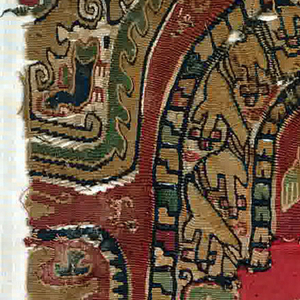 Polychrome tapestry medallion with confronted riders flanking a tree.