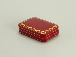 Hinged red leather box with canted corners; gold decoration.