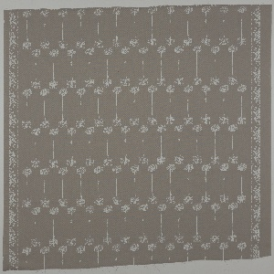 Taupe ground with design in white of off-set rows of Queen Anne's Lace. Border of lilies on two selvedge edges.