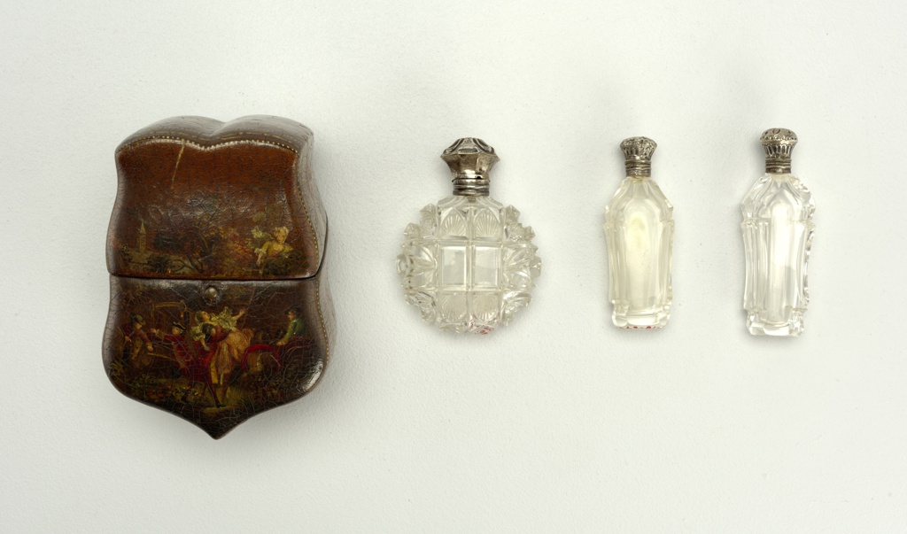 Shaped box of leather with sloping cover hinged at back containing three cut-glass scent bottles with silver tops (two have glass stoppers and one cork with silver ring). The decoration on the leather is of the type known as Vernis Martin and shows on the front an elopement scene; on the sides, trophies; and on the back, a chateau on a river. The box is lined with green velvet.