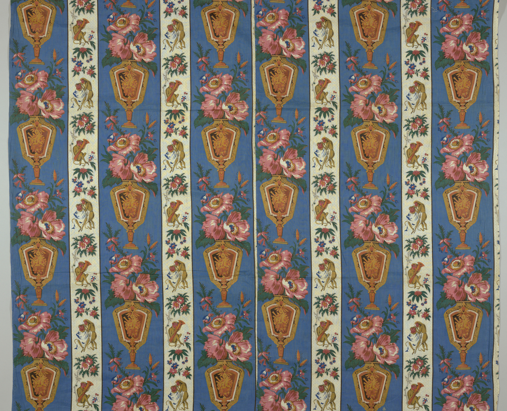 "Unlined bed cover made up of two lengths of printed fabric. Pattern composed of two stripes: the wider with an urn of flowers on a blue background. 18.5cm. wide and the other with a monkey giving another monkey a haircut alternating with a monkey playing a horn seated under a flowering plant. 9.5cm. wide. Two groups of stripes are half dropped and with an additional wide stripe fill full width of fabric. Unit of repeat: 36.5 cm. high x 28 cm. (11"") wide."