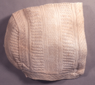 White baby's cap with bands of lace-like stitches.