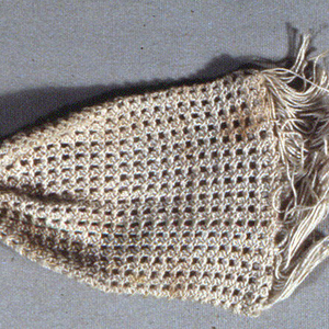 White crocheted miser's purse with ivory rings and fringed ends.