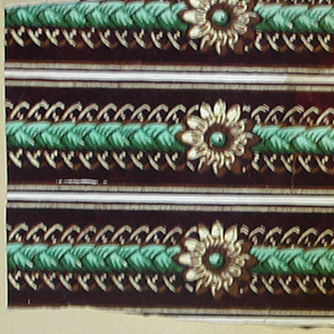 Fancy gimp with braided ribbon and floral (daisy?) boss.  Printed in green, tan and brown, on a white ground.