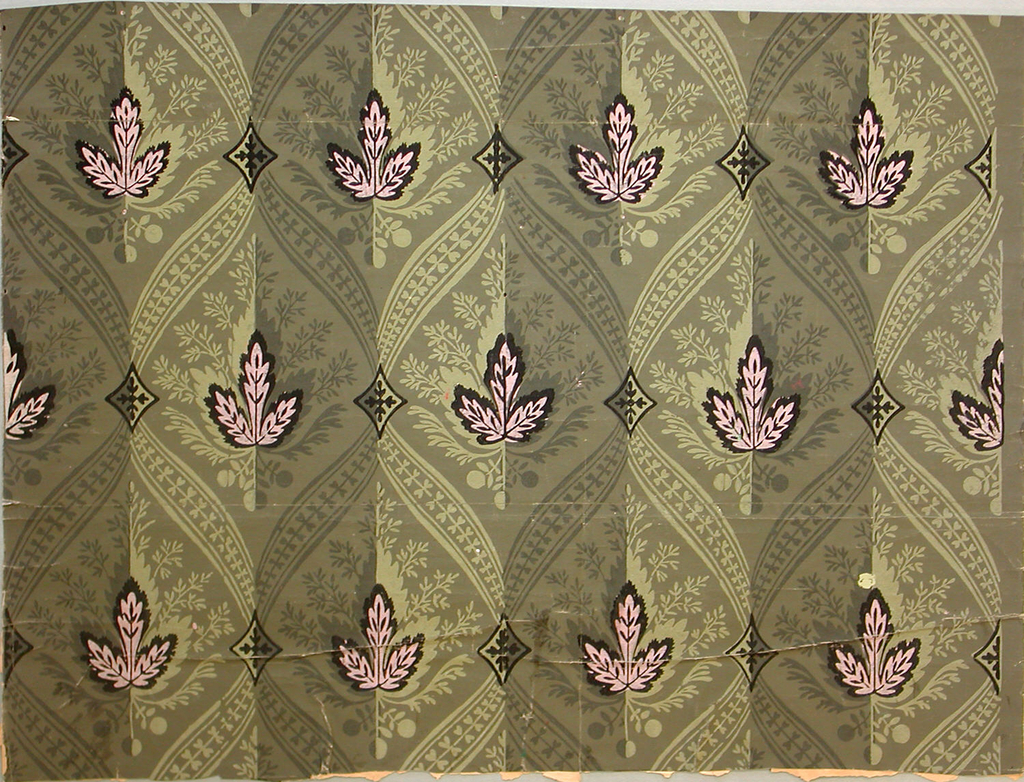 Diaper pattern composed of ribbon and bosses with inset, stylized pink leaf and shadow. Optical effect created by alternating light and dark bands of printed ornament.  Printed in black, olive and dark green, on a dark green ground.