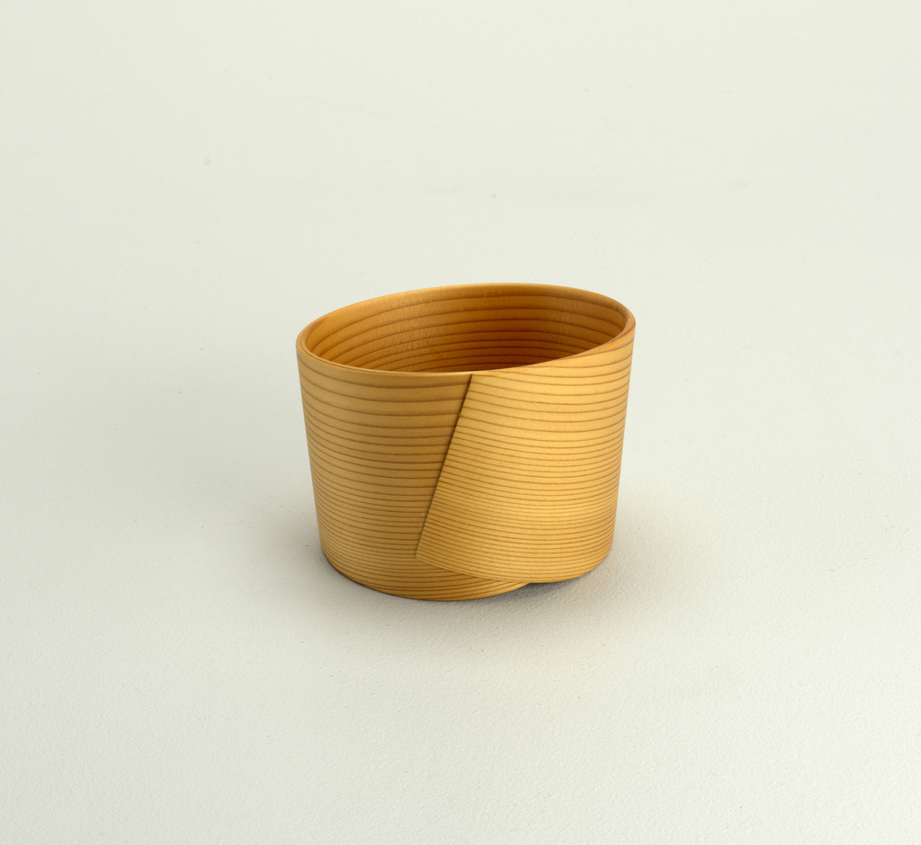 Bowl constructed of three pale, unstained cedar strips, wrapped around flat bottom to create bowl with continuous edge, rising at opposite sides to gentle point. Wrapping technique creates triangular overlay of cedar strips at opposing lower sides.