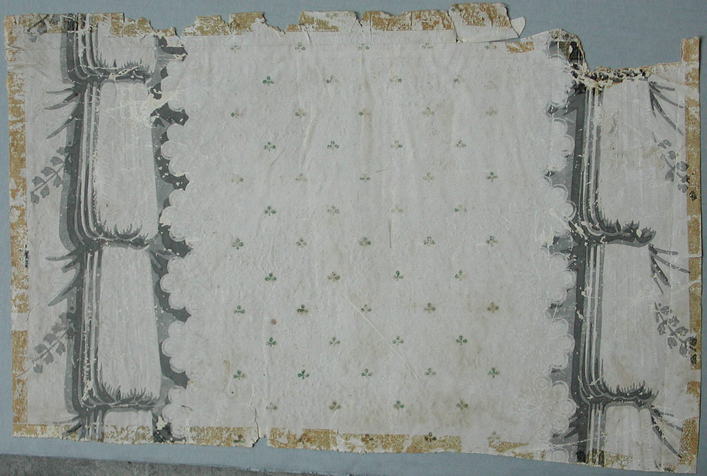 Drapery paper with lace floral motifs and green clover design in center. Bunches of fabric on either edge. Foliate swags on far edges of paper. Printed in shades of gray, white and green on off-white ground.