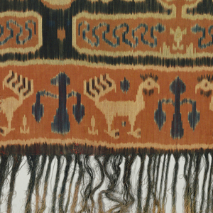 Rectangular men's ceremonial wrapper (hinggi) with patola-inspired pattern of a geometric grid composed of overlapped circles. Skull tree or 'andung' band at both ends with other bands of animals (roosters or other birds). Fringed.