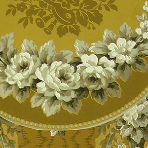 Moire stripe with festooned baskets of flowers hanging from ribbons. Scalloped border attached, festoon of roses, band of beads, trophy. Printed in yellow ochre and grey on a brown ground.