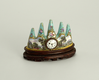 Green enamel body with five points graduating upwards from each end to center, decorated on obverse with landscape, on reverse with still life, surrounded with rocaille arabesques and flowers.   Furnished with watch movement with plain white enamelled face, surrounded by alternating red and green brilliants.