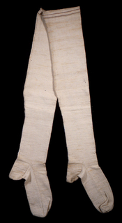 One pair of white handknit stockings with two narrow lines of reddish brown at the top.
