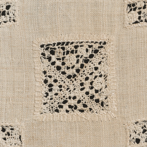 Hemstitched linen square with five squares in filet brodé set in. On one edge a pointed border of bobbin lace. On opposite edge a panel of ribbon-like serpentine flowering vine design.