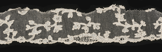 Fragment of Alençon needle lace with sprig and blossom pattern with occasional details in openwork.