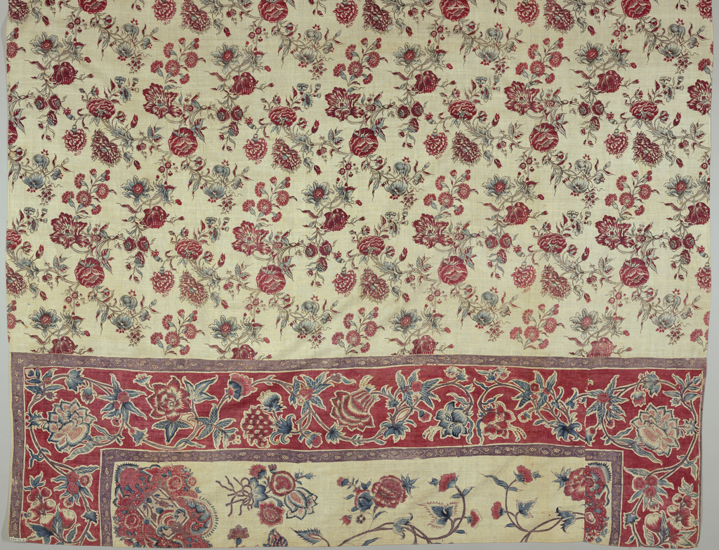 Chintz bedcover composed of a large central panel and two end pieces that have been stitched on. Floral pattern printed in red, blue and deep purple on a white ground.