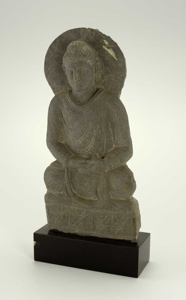 Shallow slab of grey schist carved to represent a robed Buddah with halo behind his head, seated cross-legged on rectangular support with hands in lap. Reverse is roughly finished with horizontal gouge lines. Small round hole in center back.