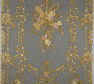 Curtain panels of black net with ochre cotton appliqué forming flowers and leaves outlined in chain stitch with tan and light brown silk or covered in chain stitch with white, pale and bright pink, yellow, tan or pale green silks. In center is a large basket with overflowing flowers and leaves suspended on two long ribbons from the top of the curtain. Sides and bottom are scalloped. Some of the centers of the blossoms have been cut out and filled with six threads knotted in the center to form spokes.