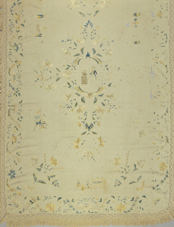 Bedcover with embroidery in a design of six scenes said to illustrate events in the life of Manuel de Godoy (1767 – 1851) with surrounding floral motifs. Embroidery in soft shades of green, blue, yellow and cream silk in satin and surface stitches. Cream-colored cotton fringe with a lattice heading and cut skirt on three sides.