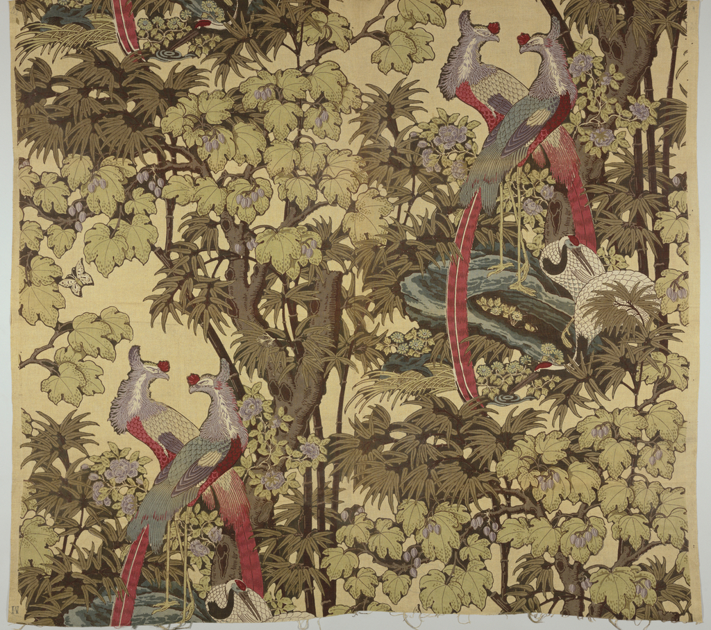 Multicolored design printed on tan natural linen shows two large exotic birds with lavender heads, red breasts, and long red tail feathers. Two large white cranes with red and grey heads and long legs stand in grey water under a large brown tree with light green leaves and lavender fruit. Long brown bamboo shoots at edge of water.