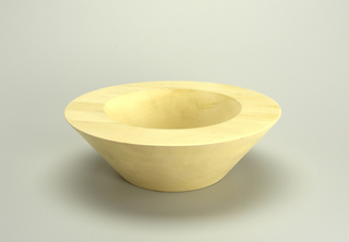 Thick-walled, inverted conical bowl with wide flat lip, circular floor.