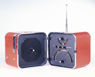 Red plastic rectangular block-like form with rounded edges and corners; retractable chrome handle, top left; sectioned retractable antenna at top, rear right corner. The body divided at center by chrome band; small button in front, hinged at back; body opens to reveal black speaker in left section, black panel with control dials and buttons in right section.