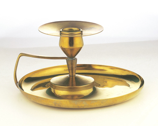 Flared candleholder sitting on a plate with enclosed handle made in brass.
