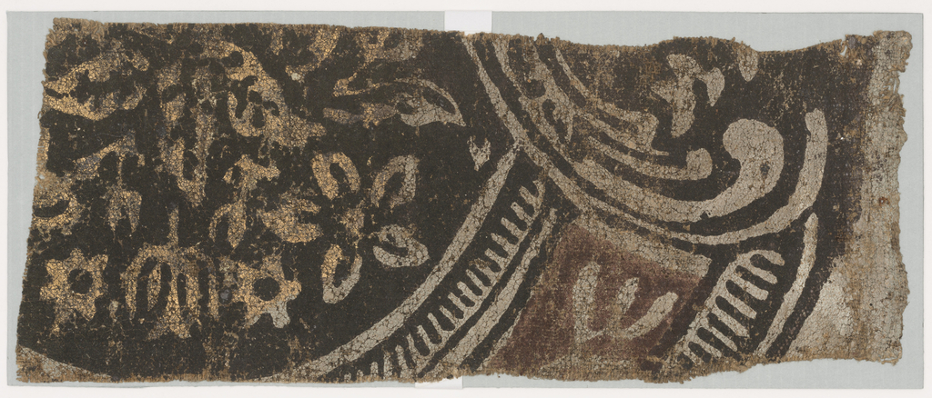 Horizontal rectangle with a fragmental pattern of stylized flowers in gold on a black flocked ground enclosed with a gray, brown and black arch and scroll. Margin at left. Printed with black and brown flock and gray and gold paint on canvas.