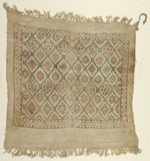 Natural linen square with patterned panel using wool filing most of it: diamond lattice enclosing geometric flowers. A small square covers the intersection of crossed diagonal lines. Narrow geometric border on 4 sides. Remains of rope tied to two corners.  (MS '77)