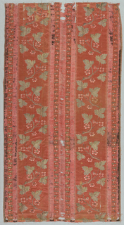 Deep coral pink satin with serpentines of silver-gilt leaves, small pink and coral flowers; set off by broad vertical stripes of dark brown warp ribbing with cherry-patterned guard-strips.  Broad pencil-striped selvages with cloth outer edges with heavy silk warps.  Lined with undyed glazed linen.  Pocket.  Rows of buttonholed coral silk loops across upper and lower part.